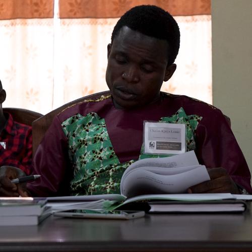 Sierra Leonean teacher, Charles, reads through the handouts before a lecture